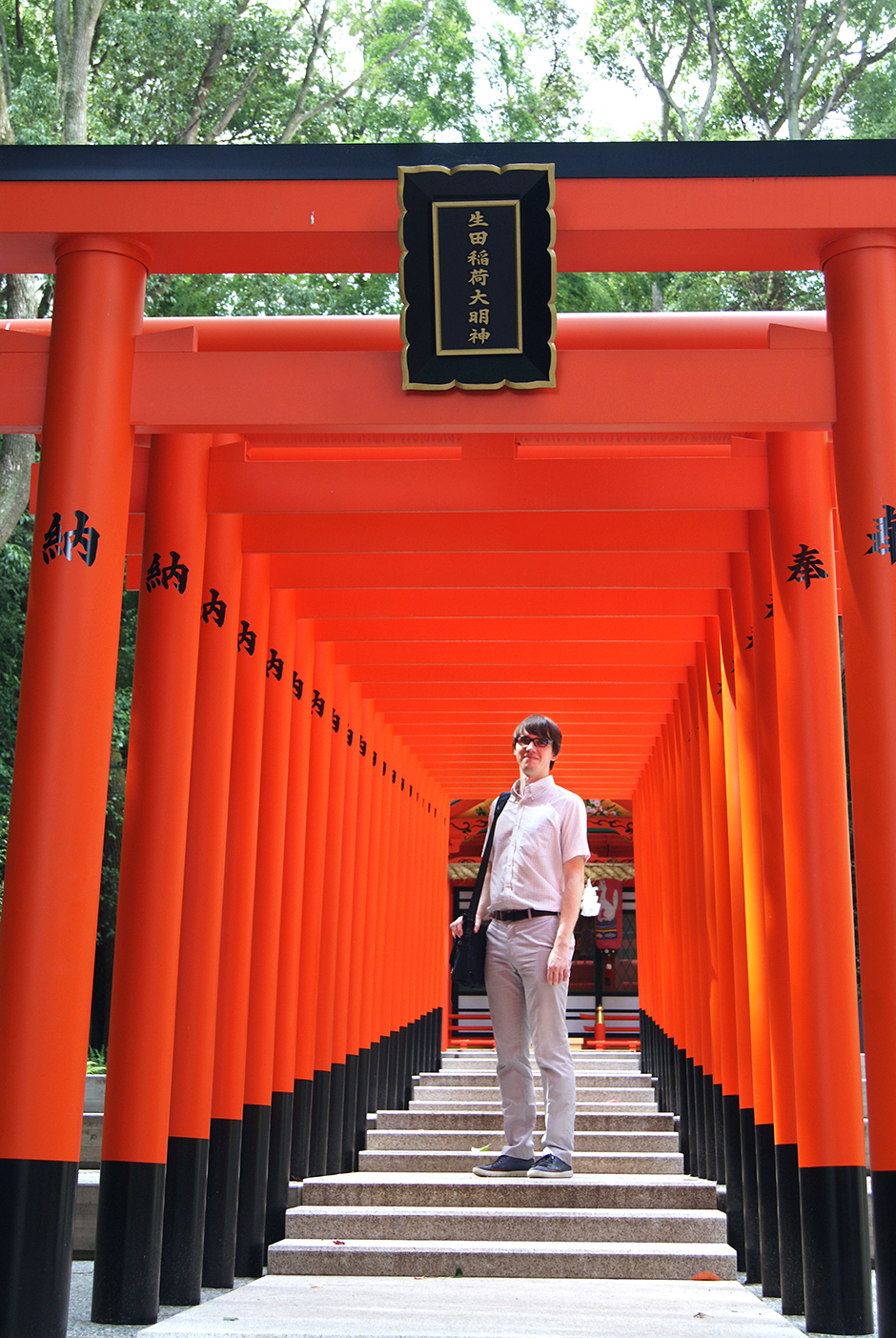 You don't need to go to Kyoto to take a photo like this. There's a short path of bright red tori gates right behind Ikuta shrine.